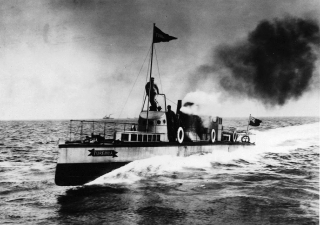 A black-and-white photograph of a steam-powered boat at speed at sea