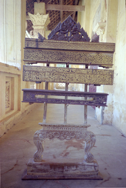 A wooden manuscript rack with carved decorations found in Pakse, Champassak Province, Laos. On the rack are four wooden manuscript boxes. Photograph by Harald Hundius. Courtesy of Preservation of Lao Manuscripts Programme (PLMP), © National Library of Laos.