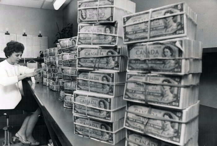 Bank are money; and assistant teller Mrs. June Gora of the Bank of Montreal is shown here with about $200;000 of it. Mrs. Gora works in a top-security vault in the bank's main Toronto Branch and handles millions of dollars a week. The stacks of money here are being prepared for shipment to smaller Metro-area branches. Cash receipts front various special customers; such as the Toronto Transit Commission are also counted and processed here. Canadians have more than $24 billion on deposit with the chartered banks and less than $3;000;000 of it circulating.