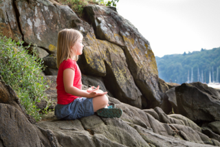 Girl meditating on a rock