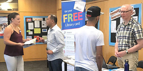 Library staff talk to business college students