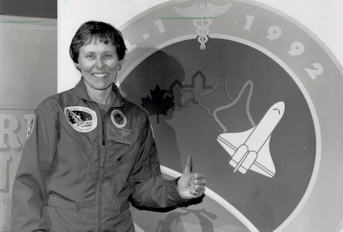 Roberta Bondar in space jumper infront of a space-inspired mural