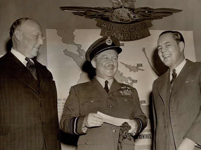 Billy Bishop standing beside two men in front of map