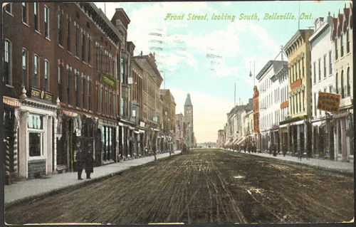 A main dirt road with three story buildings towering above it on both sides