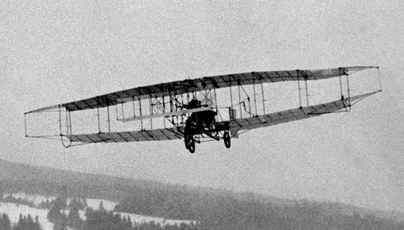 Silver dart plane mid-air
