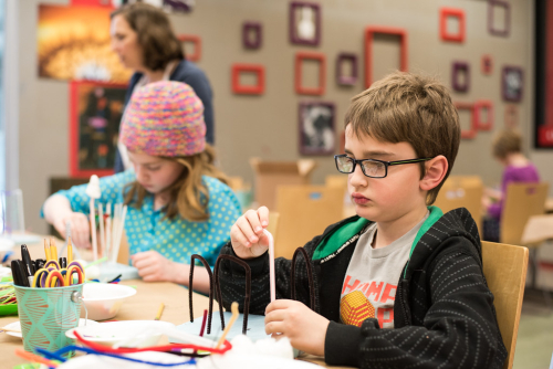 Two children sitting at a table building an object with pipecleaners