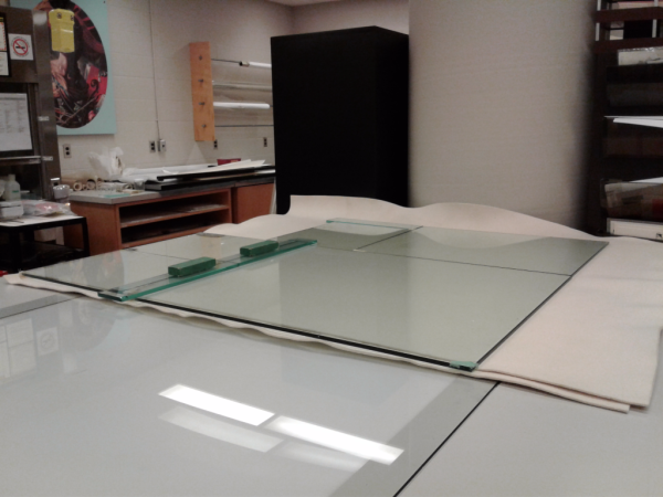 Large glass panel on top of papers in conservation lab